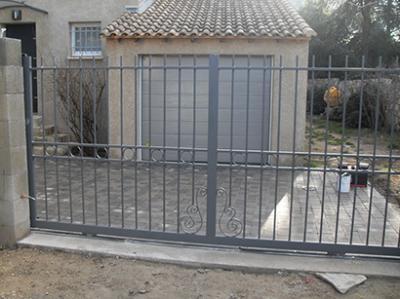Portail fer forg avec des volutes gard for Petit portail fer forge